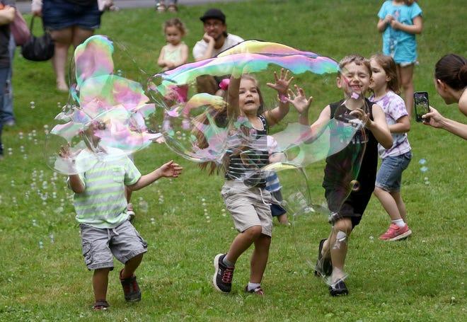 Desita Robbins, 4, center, and other children race Saturday, June 19, 2021, toward the large bubbles made by Rodman Public Library's James Sedoris during a Bubble Bonanza program.