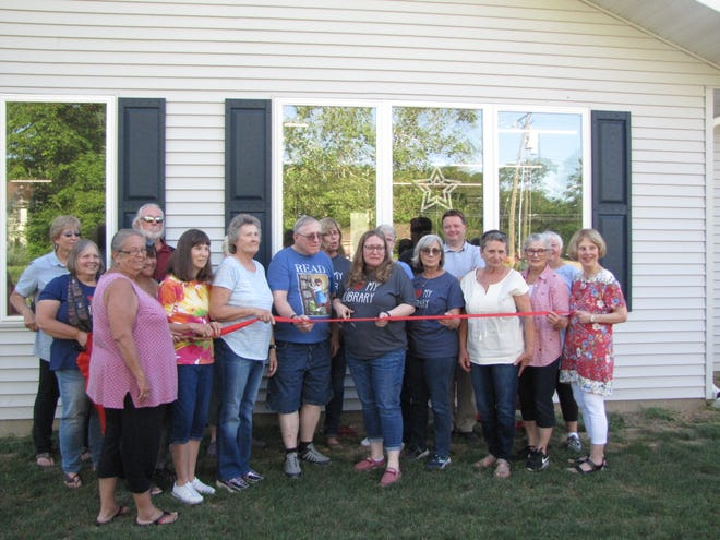 Pictured are members of the Lewistown Chamber of Commerce and members of the Carnegie Library Board cutting the ribbon designating the grand opening of the new library site.