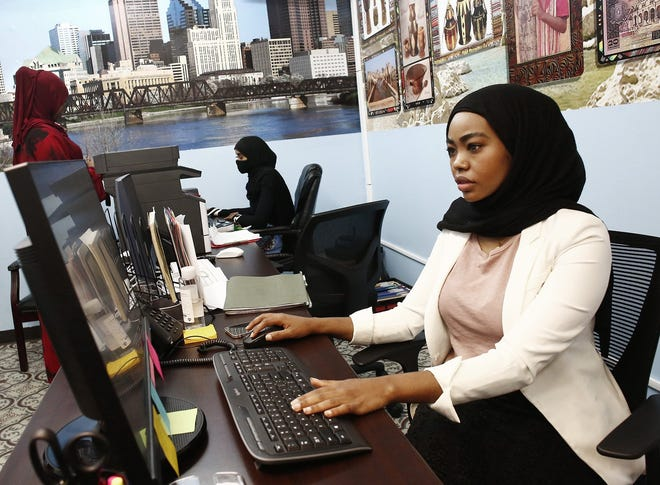 Hindo Salad, Director of Businesses, background, and Asma Ali, Director of Housing, foreground, work in the office at The Somali Community Link on May 3, 2021. A majority of Somali immigrants to the Columbus area have started their own businesses, according to economic development experts.