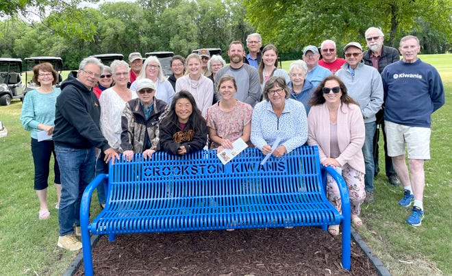 Odine Smulan's kids and grandkids, Kiwanis members and others gather around the new bench at Minakwa Golf Course.