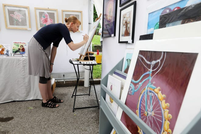 Illustrator and artist Kelsey Wilson works on a drawing in her her booth Sunday at the Snake Alley Art Fair in Burlington. This year's fair featured 65 regional artist in 81 booths.