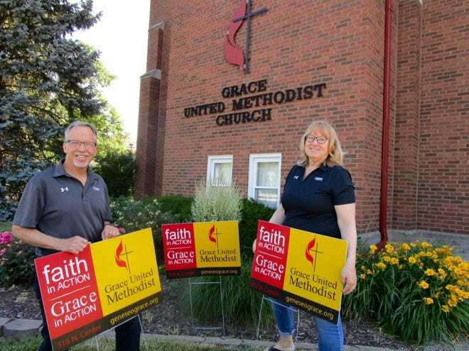 The Rev. Mark Graham, co-pastor at Grace United Methodist Church in Geneseo; and Jackie Mickley, chairman of the church's Grace in Action Sunday, have the yard signs that will be placed at various locations in Geneseo on Sunday, June 27.
