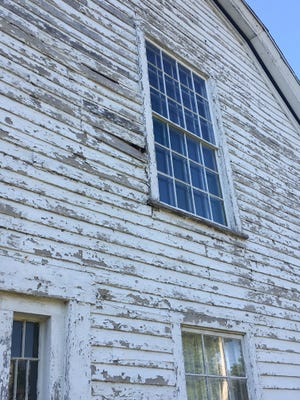 Chipped paint and loose siding are seen on the Colony Church in Bishop Hill. A resident is trying to call attention to dilapidated state-owned buildings in the historic village.