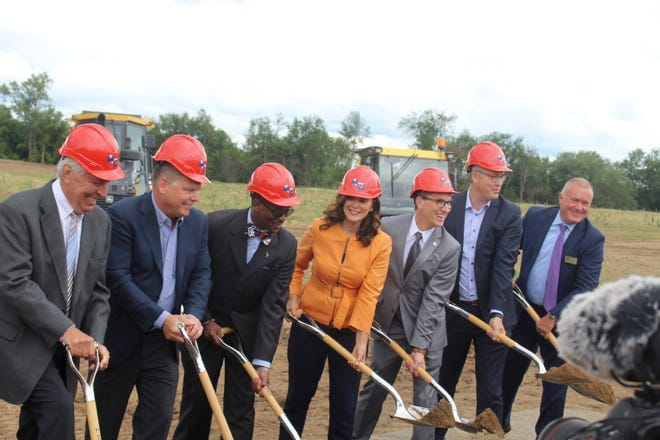 Business and state officials, including Michigan Gov. Gretchen Whitmer, participate in a ceremonial groundbreaking for a new facility for industrial shelving company Speedrack on Monday, June 21, 2021, in Walker, Mich.