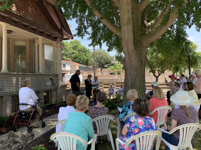 Members of Illinois State Daughters of the American Revolution watch as DAR Regent Sharla Luken presents a donation for the cottage restoration work at a public ceremony on June 17.