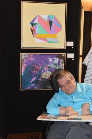 Harvey Colish  proudly exhibits one of his laser point creations.