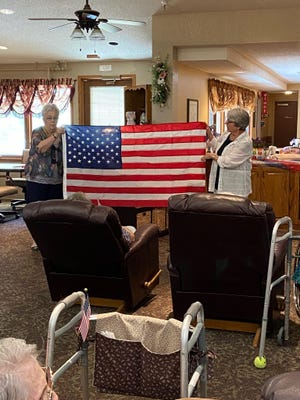 Jean Harrison and Barbara Grimmett hold up the flag of the United States of America for celebration and reverance at the Leisure Home in Stafford on Flag Day.