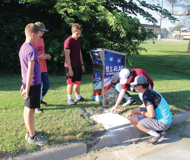 Luke Schmidt (second from right) places nuts and bolts in place that will secure a new flag retirement receptacle in place on Third Street in front of the American Legion building. He was assisted last Monday by fellow Boy Scout Troop 201 members (from left) Ryan Haas, Cohen Flanders, Addison Hopkins and Cade Hopkins.