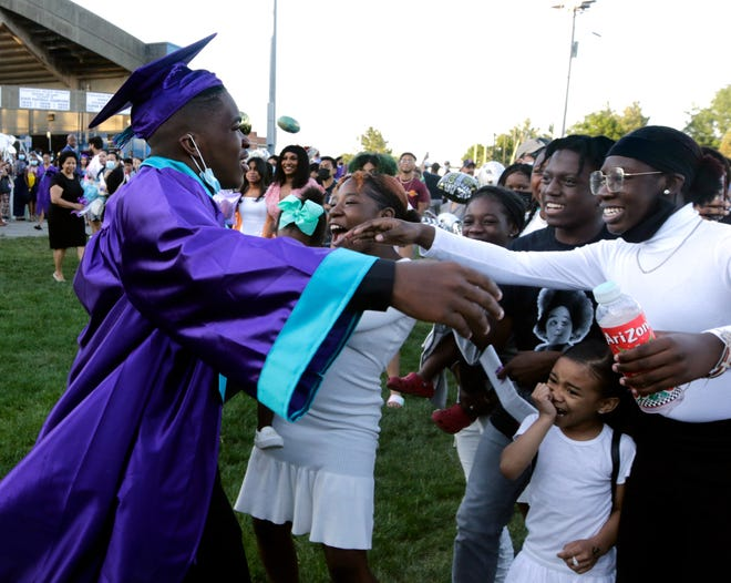 Providence Career & Technical Academy's Isaiah Johnson reaches out to embrace family members who are racing to congratulate the new graduate.