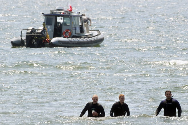 Warwick police divers, from left, Tom Greene, Ben Bratko and Jonathan Byrne walk to shore after searching Monday. Byrne found the body of 10-year-old YosekarlyMartinez of Providence, who succumbed to the strong currents around Conimicut Point on Sunday.