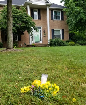 Flowers and a single candle were placed in front of the Mavrakis family home where four family members were found dead Sunday in a suspected domestic dispute.