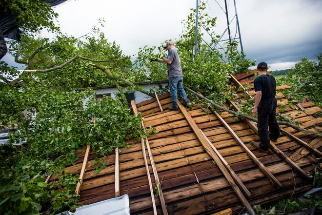 Brandon White, left, and Dakota Collins work on cleaning up damage from an overnight storm Monday, June 21, 2021 at a home near the intersection of Osborne and Gumwood Roads.
