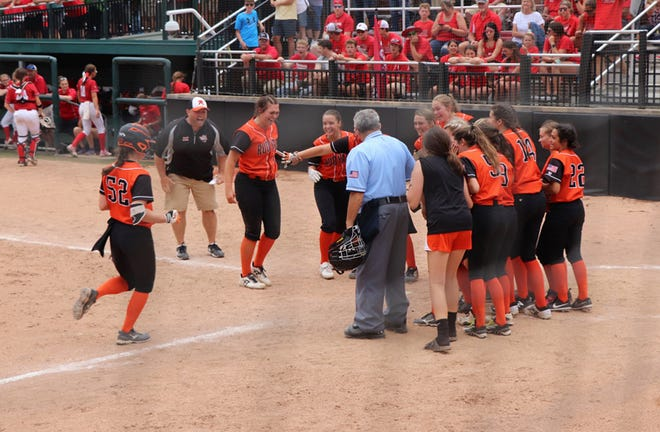 Rudyard's Morgan Bickel (52) heads towards home plate and is greeted by her teammates after hitting a walk-off home run as the Bulldogs beat Holton 9-8 in nine innings in the semifinals at MSU Friday.