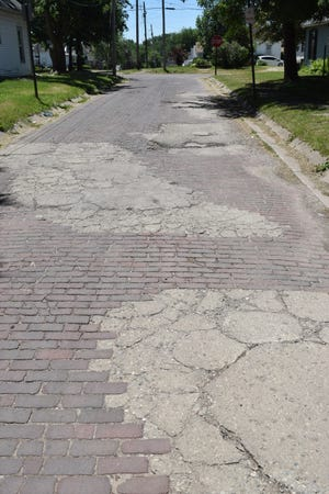 Much of Franklin Street's brick pavement has been repaired with asphalt patches — making the street even rougher than it had been.