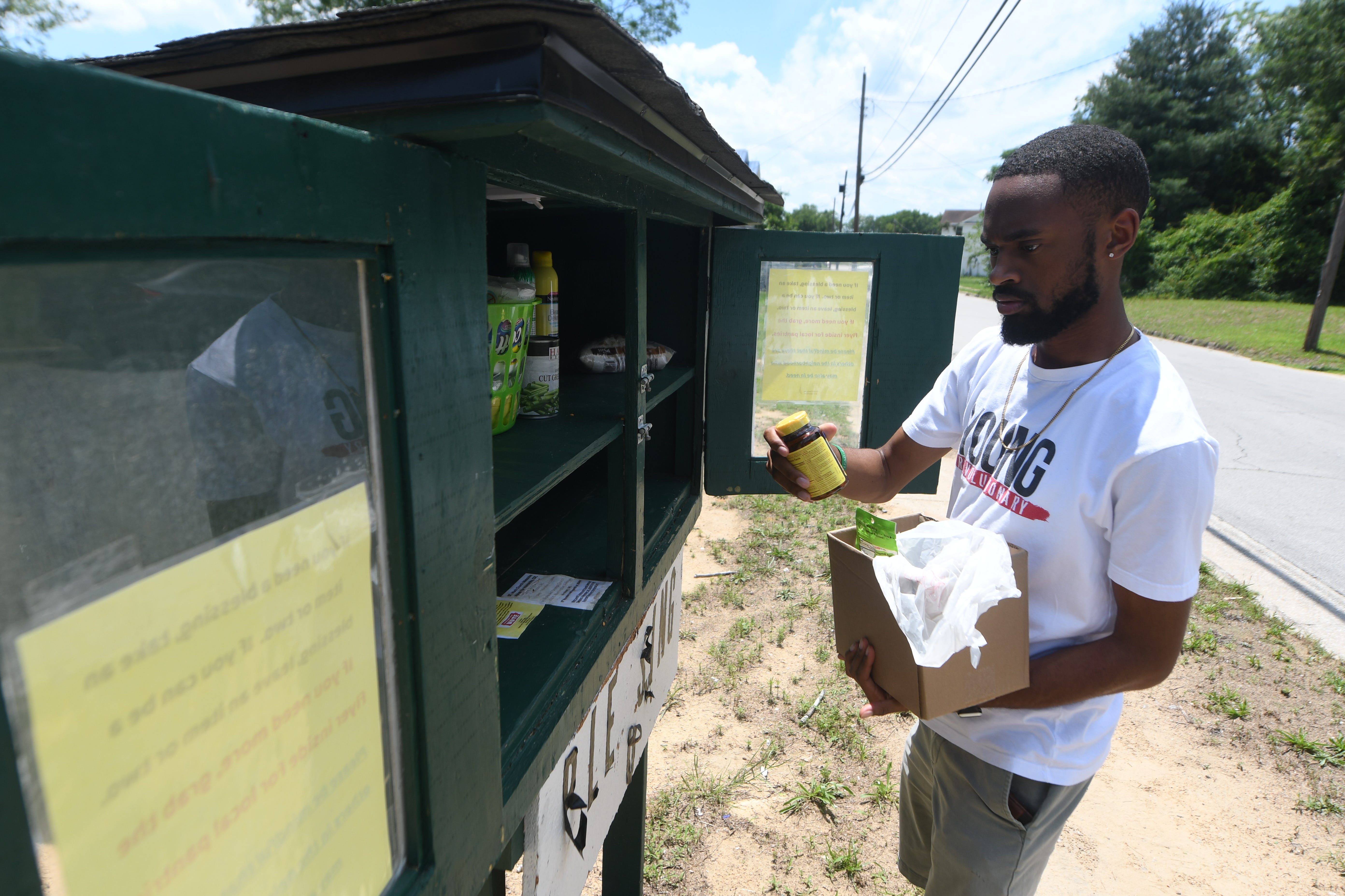 """Chris Suggs restocks the blessing box that he started though his Kinston Teens charity in Kinston, N.C., Wednesday, June 16, 2021. The box is a way for community members to donate and get various things like food and toiletries. Chris Suggs is the founder and executive director of the non-profit that started in 2014. East Kinston is one of the poorest neighborhoods in North Carolina, according to the U.S. Census Bureau, and has been declared a """"food desert"""" by the U.S. Department of Agriculture.   [MATT BORN/STARNEWS]"""