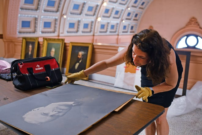 Deborah LaCamera art conservator of Studio TKM Associates works on a portrait in a hallway at Worcester City Hall on Monday.