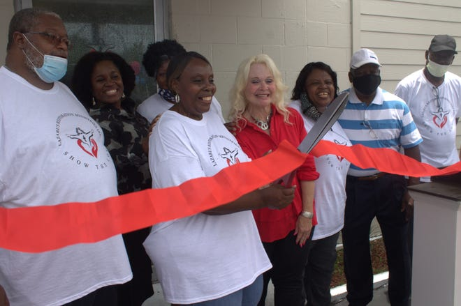Priscilla Young, outreach manager for the Lazarus Restoration Ministries' Life Center, cuts the ribbon during the center's grand opening.