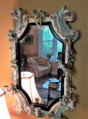 This wall-mounted mirror has an ornately decorated porcelain frame depicting birds and foliage. [Submitted photo]