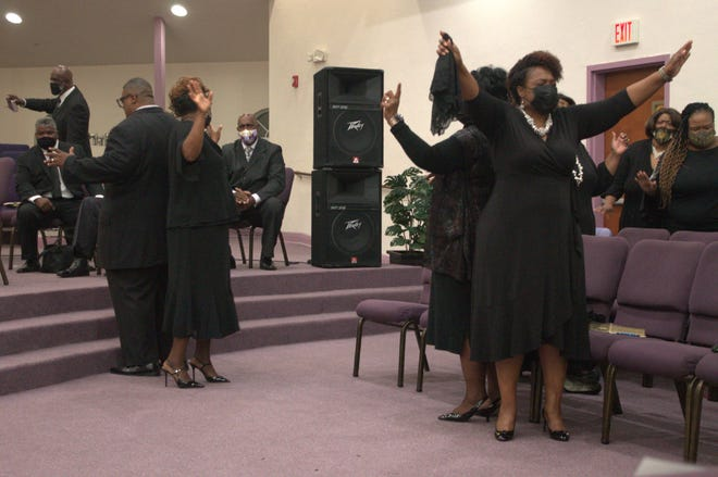 Parishioners stand back-to-back signifying how God has their back through trying times during the final service of the COGIC Florida Central 2nd Ecclesiastical Jurisdiction's 2021 Auxiliaries in Ministry held at Upper Room Ministries in northeast Gainesville.