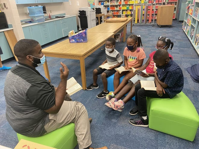 Dreall Williams, who volunteers at Lake Forest Elementary, is pictured reading with an after-school reading group at Lake Forest Elementary.