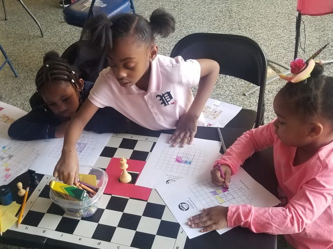 Janai Richardson, center, teaches other young students how to find patterns on a chessboard during a Saturday Morning Lights chess event in Poughkeepsie just prior to the pandemic.