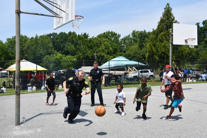 Asheboro officers Spencer Hamilton and Mason Byers play a pick-up game with kids at Asheboro's Juneteenth event.
