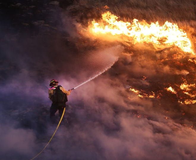 Firefighter works through smoke and gusty winds to knock down fire.