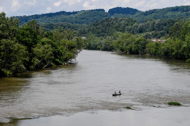 People paddle up the French Broad River in a canoe near the location of the future Woodfin Wave June 21, 2021. Recent code changes have opponents of a proposed riverside development crying foul, saying they'll make it easier for large developments in the future.