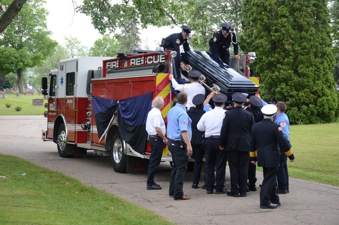 """Firefighters from several departments lift the casket of David """"Bud"""" Dunn from an Emmett Township fire engine before his burial on Monday."""