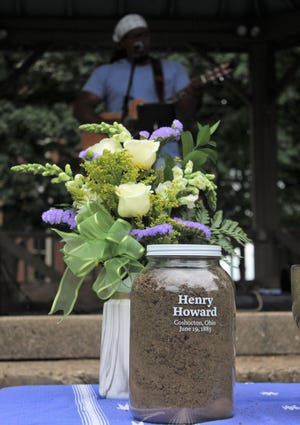 Musician Rese Jhordan plays guitar behind a jar of soil memorializing lynching victim Henry Howard during the Juneteenth event Saturday on the Coshocton Court Square.