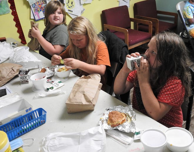 Helena Pettit, 9, Amaya Endsley, 8, and Kinley Hardesty, 7, have lunch at the Chestnut Crossing Learning Center at Chestnut Crossing Apartments. The center is a distribution point for a summer meals program by the USDA and administered locally by Kno-Ho-Co Ashland Community Action Commission.