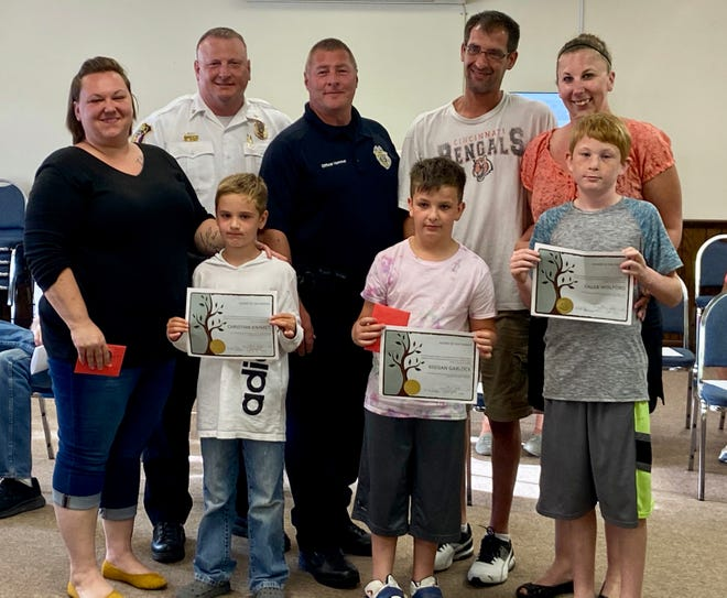 Pictured with Oak Harbor Police Chief Eric Parker and SRO Officer Dean Hammer are Linda Brooks with son Christian Kimmet and parents Michael Garlock and Bethany Paul with Keegan Garlock and Caleb Wolford. The students were awarded Great Citizenship awards at a recent Oak Harbor City Council meeting.