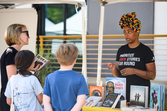Tamika Thompson of Beyond This February, an independent online bookstore that features black authors and stories, chats with a family at the Third Thursday Market in Poe West on Friday, June 18, 2021.