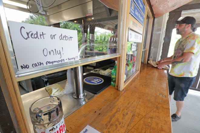A sign informs customers that only credit or debit cards, and not cash, are accepted forms of payment as Trevor Gullion, of Milwaukee, picks up an order at Estabrook beer garden in Milwaukee on Monday, June 21, 2021.