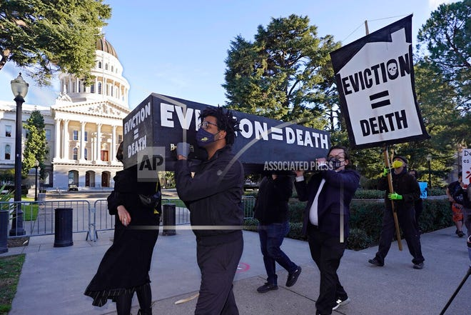 In this Jan. 25, 2021, file photo, demonstrators call passage of rent forgiveness and stronger eviction protections legislation and carry a mock casket past the Capitol in Sacramento, Calif. California Gov. Gavin Newsom and state legislative leaders are negotiating about whether to extend the state's ban on evictions for unpaid rent. California's eviction protections will expire on June 30. Newsom has proposed using federal coronavirus aid money to pay off 100% of the rent people owe. (AP Photo/Rich Pedroncelli, File)
