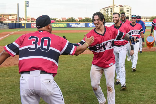 The Pensacola Blue Wahoos celebrate an extra-inning walk-off victory on Father's Day at Blue Wahoos Stadium on June 20, 2021.