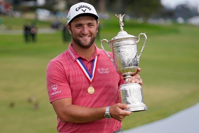 Jon Rahm, of Spain, holds the champions trophy for photographers after the final round of the U.S. Open Golf Championship, Sunday, June 20, 2021, at Torrey Pines Golf Course in San Diego. (AP Photo/Marcio Jose Sanchez)