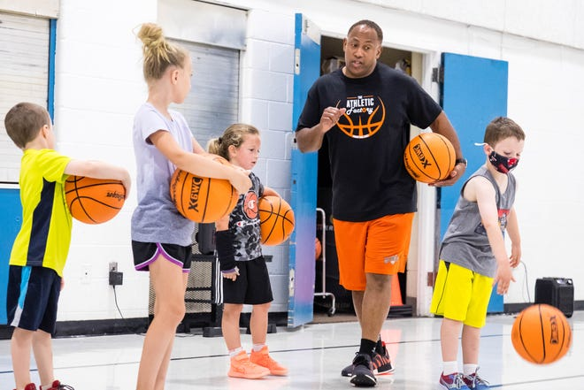 Cliff Thomason, who founded The Athletic Factory, leads a group of kids in a warmup during a Biddy Ball session Saturday, June 19, 2021, in Port Huron. Biddy Ball is a program hosted by The Athletic Factory to help introduce first- and second-graders to basketball.
