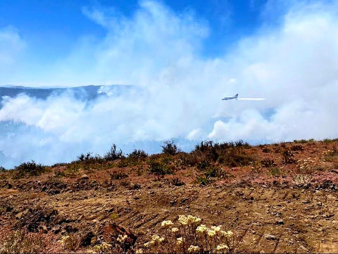 An air tanker drops water on the Warm Springs Reservation S-503 Fire burning southeast of Mount Hood.