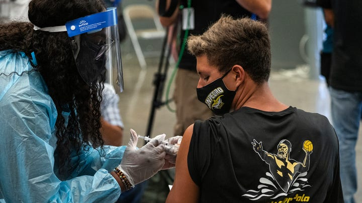 High school student William Hatch is vaccinated at a school-based COVID-19 vaccination clinic for students 12 and older in San Pedro, California.