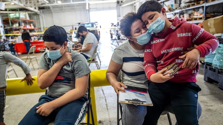 Indira Cisneron holds her son German Vazquez, right, while waiting to get her first COVID-19 vaccine shot as her other son Gabriel Vasquez, left, 13, sits and wait in southwest Detroit.