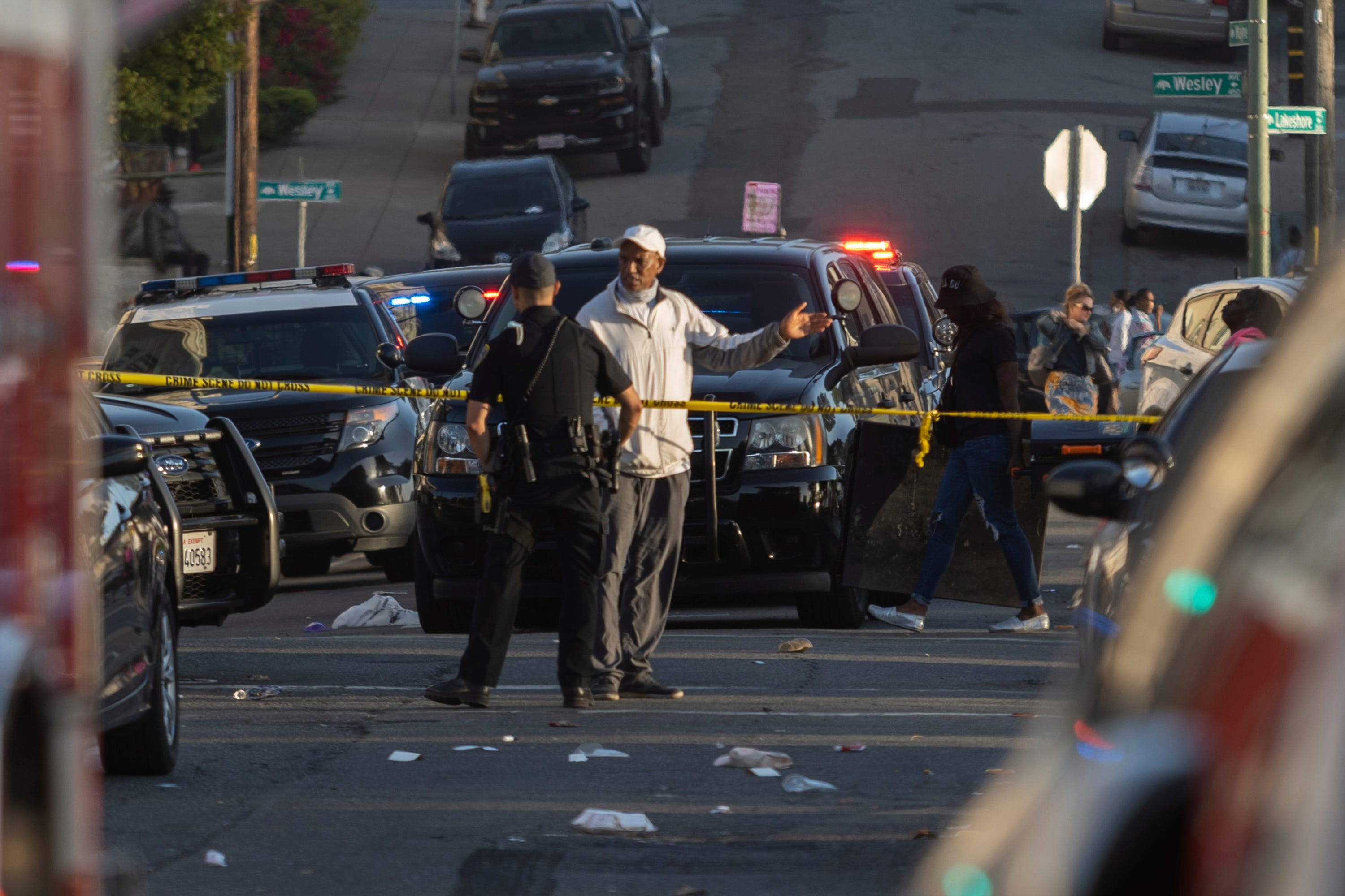 Officers work the scene of a shooting in Oakland, Calif., June 19, 2021, when a 22-year-old man was killed and five others wounded.