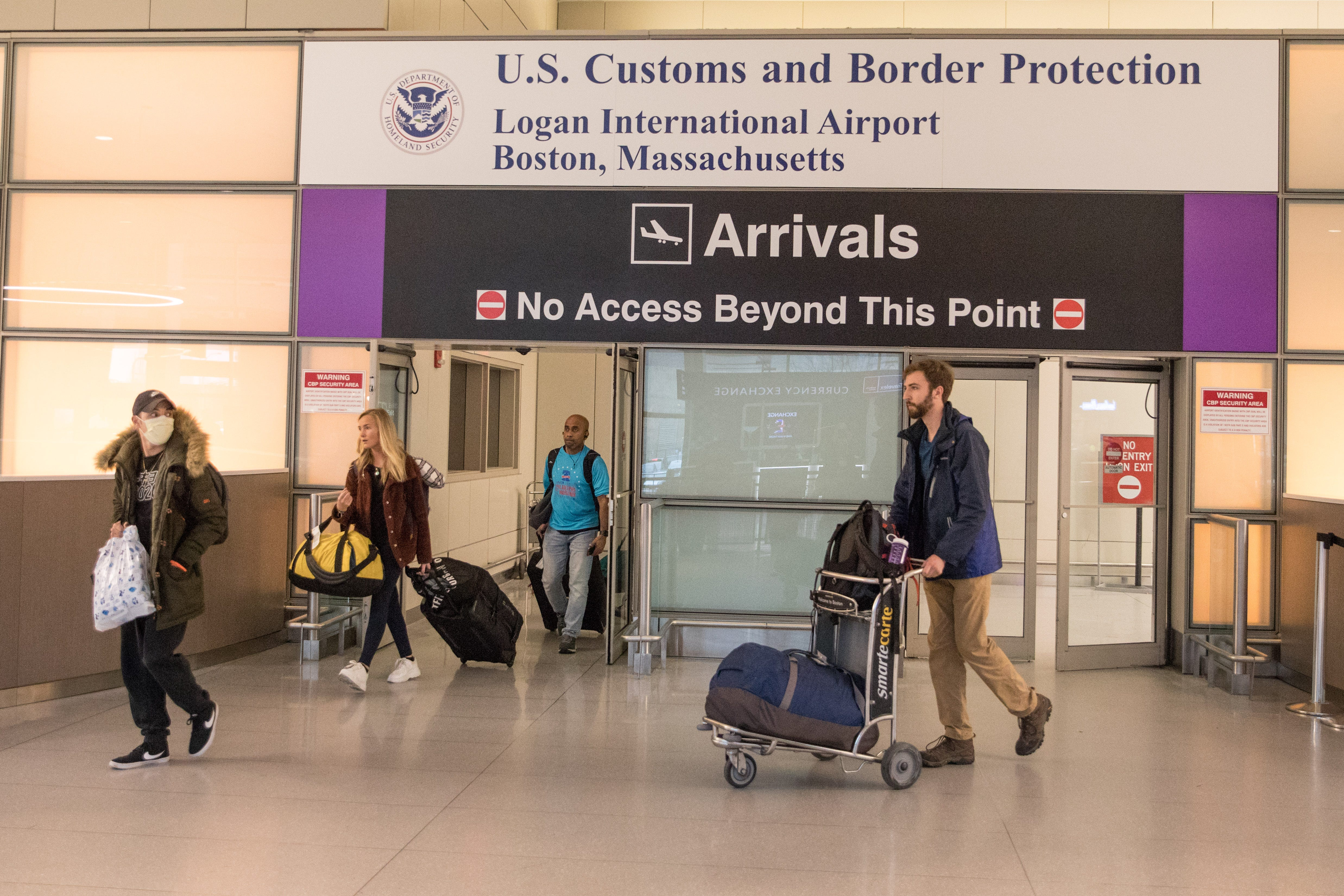 Passengers leave the secure area in the arrivals area of the international terminal at Logan Airport on March 13, 2020, in Boston.