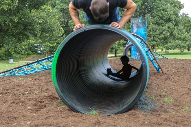"""Brock Mclean, top, and his son Case, bottom, play Tuesday in the """"Territories"""" art installation at the Butler Hike and Bike Trail on Lady Bird Lake."""