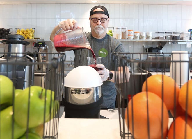 Ron Todys, the general manager, makes a smoothie for a customer at the new Beyond Juicery + Eatery in Green.