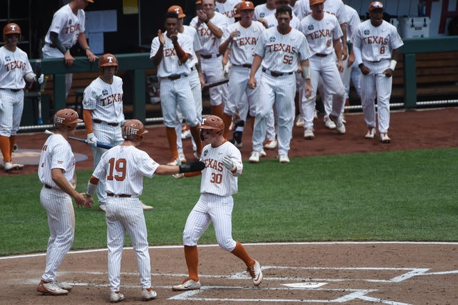 Texas outfielder Eric Kennedy celebrates with Mitchell Daly as he crosses home plate after hitting a home run in the second inning. The Longhorns now will face either Virginia or Mississippi State on Thursday night.