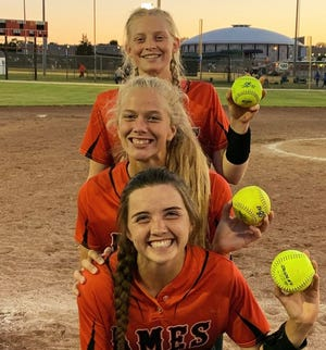Ames softball players Ellie Lynch (front), Ireland Buss (center) and Katie Riesselman hold up their home run balls after they each went deep in a doubleheader with Marshalltown Monday at Marshalltown. Ames swept both games with the Bobcats, 16-3 and 13-5.