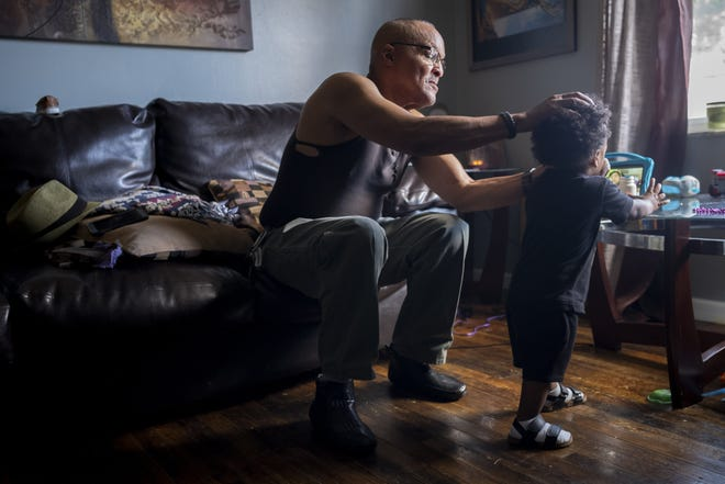 Randy Brown wipes the nose of his 20-month-old son G'ian while he's home from day care Tuesday at their home on Columbus' East Side. Brown, 67, is in recovery from a drug and alcohol addiction and has family members that are battling addiction.
