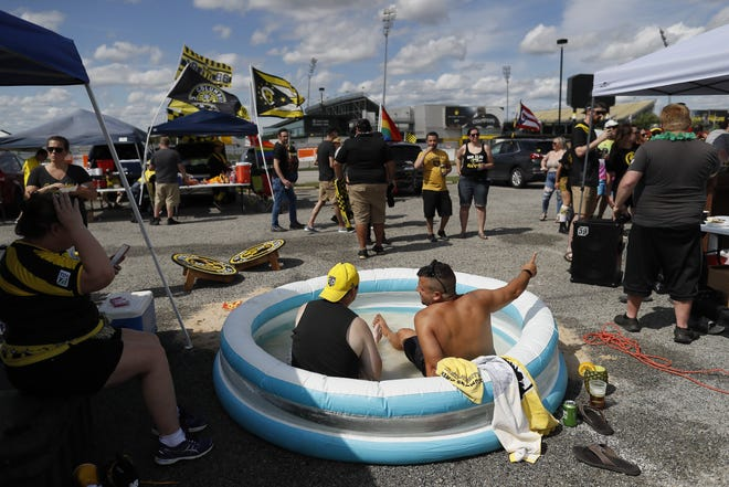 Jeff Niesing (left) of Hilliard and Zachaery Hatcher of Toledo sit in a pool at the Yellow Nation Army tailgate.