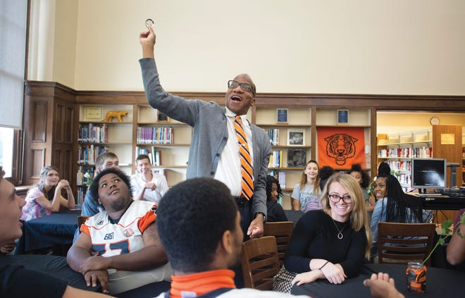 """Wil Haygood holds up a button promoting his """"Tigerland"""" book during an event where Big Walnut High School students visited East High School in 2018."""
